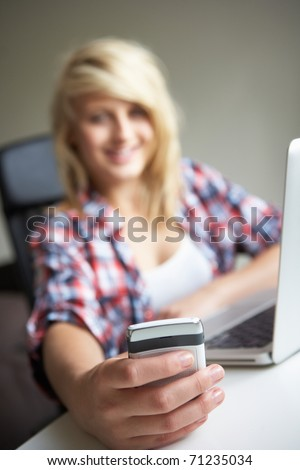 Teenage Girl Using Laptop And Mobile At Home - stock photo