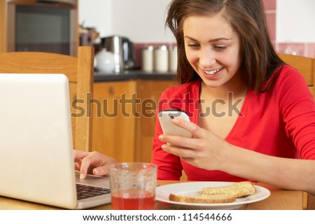 Teenage Girl Using Laptop And Mobile Phone Whilst Eating Breakfast - stock photo