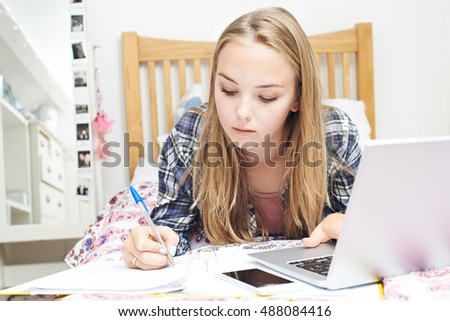 Teenage Girl Using Laptop To Do Homework In Bedroom