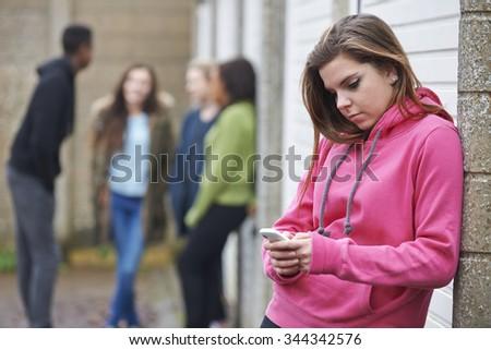 Teenage Girl Using Mobile Phone In Urban Setting - stock photo