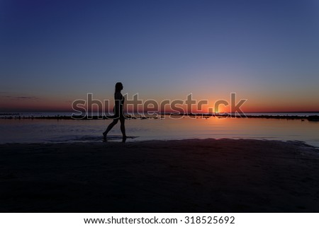 teenage girl walking in water on beach in sunset, silhouette photo