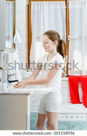 Teenage girl washing her hands in the bathroom