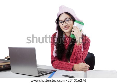 Teenage girl wearing a winter knitted clothes, doing schoolwork and smiling at the camera while holding a cup of warm coffee - stock photo