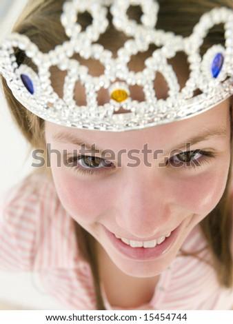 Teenage girl wearing crown and smiling - stock photo