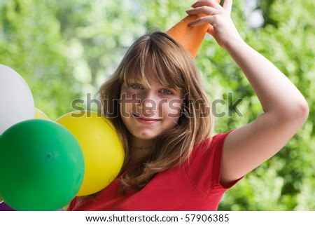 Teenage girl wearing party hat, holding balloons, Portrait - stock photo