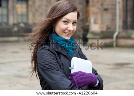 Teenage girl with a book outside the building