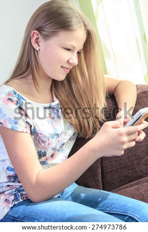 teenage girl with a cellphone at home