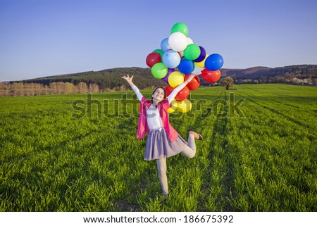 teenage girl with balloons in green field - stock photo