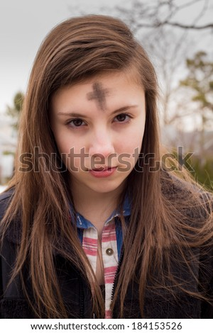 Teenage girl with cross on forehead in observance of Ash Wednesday - stock photo