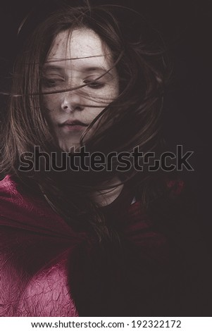 Teenage girl with hair in the wind and birds head paper, origami - stock photo