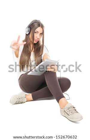 Teenage girl with headphones and tablet pc showing two fingers  - stock photo