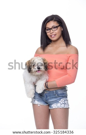 Teenage girl with her dog against a white background. She is wearing summery clothes and is looking at the camera.  - stock photo