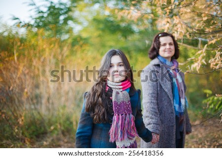 Teenage girl with her mother walking outdoors. - stock photo