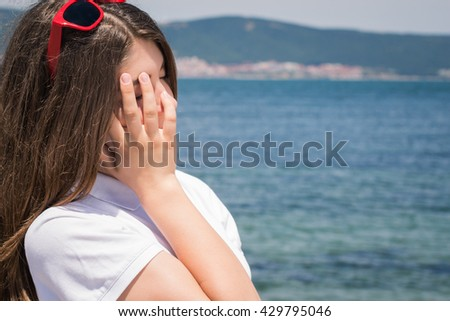 Teenage girl with red sunglasses relaxing near seaside
