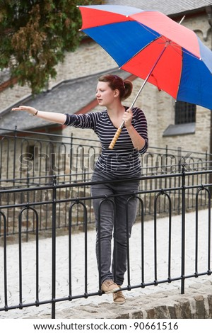 Teenage girl with umbrella waiting for rain - stock photo