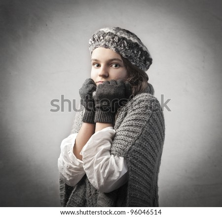 Teenage girl wrapping herself in warm clothes - stock photo