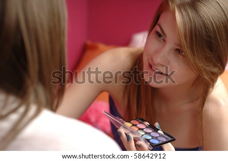 Teenage girls apply make up in their room. - stock photo