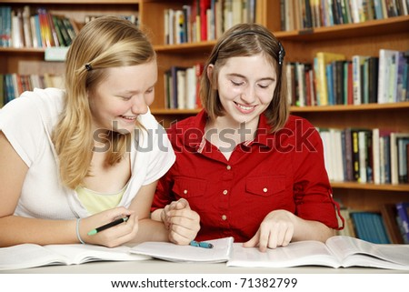 Teenage girls in the school library, doing their homework. - stock photo