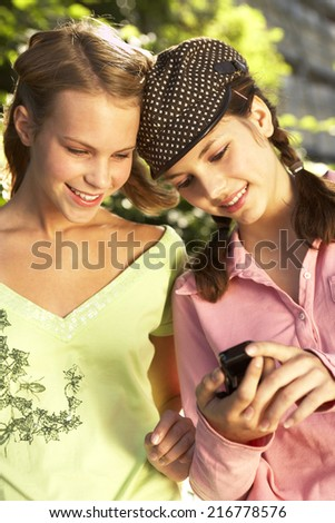 Teenage girls looking at a mobile phone. - stock photo
