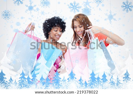 Teenage girls looking at each others purchases against snowflakes and fir trees - stock photo