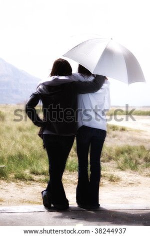 Teenage Girls Looking Out the Door with an Umbrella - stock photo