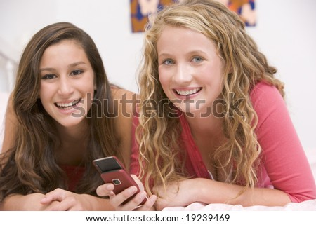 Teenage Girls Lying On Bed Texting - stock photo