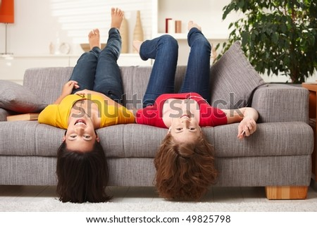 Teenage girls lying on couch upside down, looking at camera, smiling. - stock photo