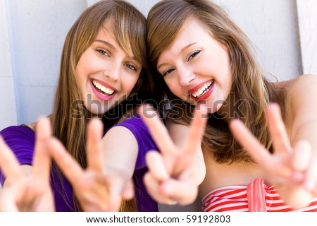 Teenage girls making a peace sign