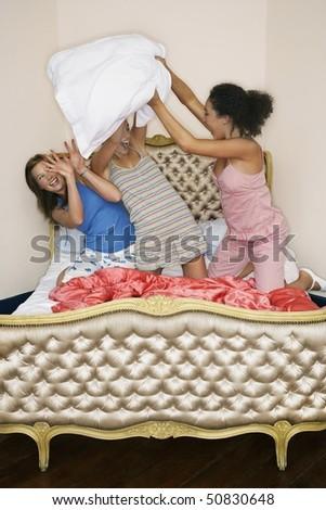 Teenage Girls pillow fighting, kneeling on funky bed - stock photo