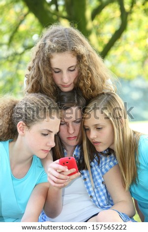 Teenage girls reading an sms message as they group together around a mobile phone outdoors in the park
