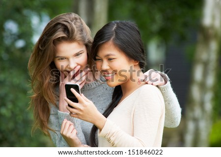 Teenage Girls Reading Text Message Together - stock photo