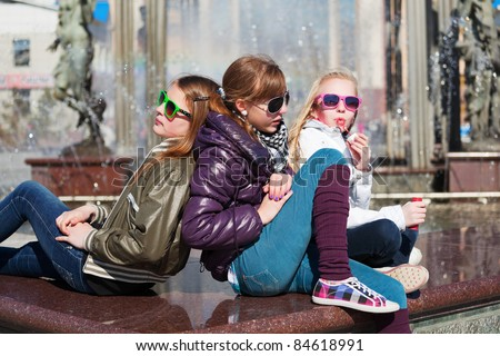 Teenage girls relaxing on a city street - stock photo