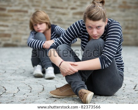 Teenage girls sitting on grounds, turned away from one another