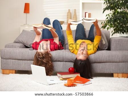Teenage girls sitting upside down on sofa reading books.? - stock photo