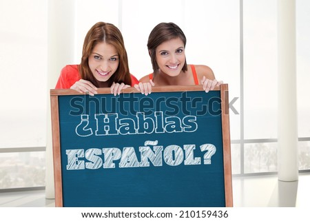 Teenage girls smiling while holding a blank poster and hiding behind it against blackboard with copy space on wooden board, Do you speak Spanish? - stock photo