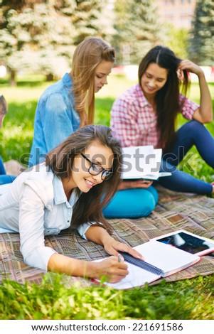 Teenage girls studying outdoors - stock photo