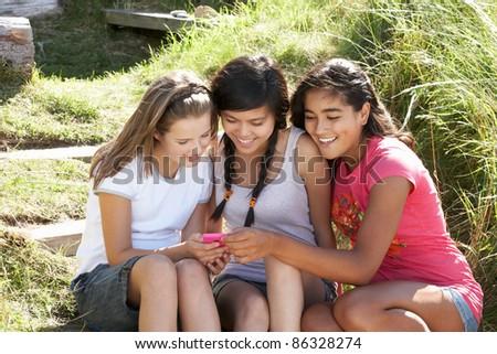Teenage girls using phone outdoors - stock photo