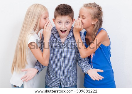 Teenage girls whispering in the ears of a secret teen boy on white background - stock photo