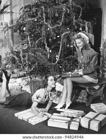 Teenage girls with presents and Christmas tree - stock photo