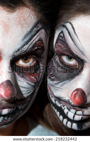 Teenage girls with scary clown face painting - stock photo