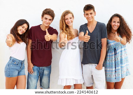 Teenage Group Leaning Against Wall Giving Thumbs Up