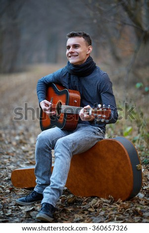 Teenage guitar player singing in the forest on an alley - stock photo