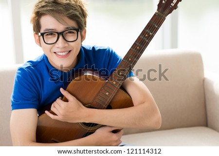Teenage guy holding a guitar and looking at camera with a smile - stock photo