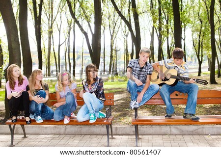 Teenage guy playing guitar, his friends listening - stock photo