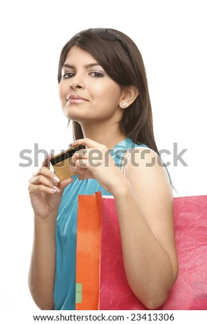 Teenage indian girl with the credit card carrying the shopping bags - stock photo