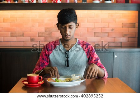 teenage indian male eating at cafe - stock photo
