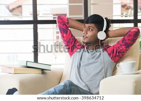 teenage Indian male listening to music - stock photo
