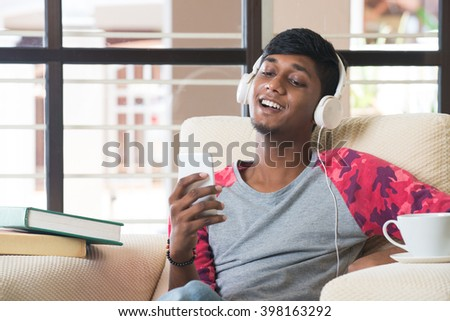 teenage indian male listening to music via smartphone - stock photo