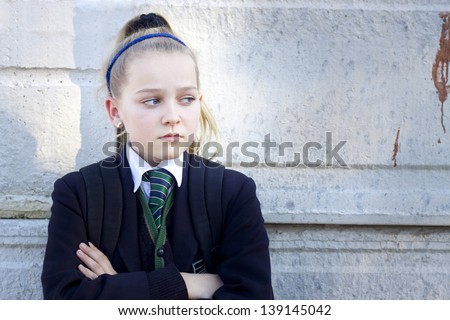 Teenage kid in school uniform looking angry, standing against a concrete wall with graffiti. Real people, candid shot - stock photo