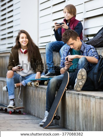 Teenage males and girl relaxing with cell phones on the street - stock photo